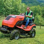 man cutting grass in a field on a sit on mower